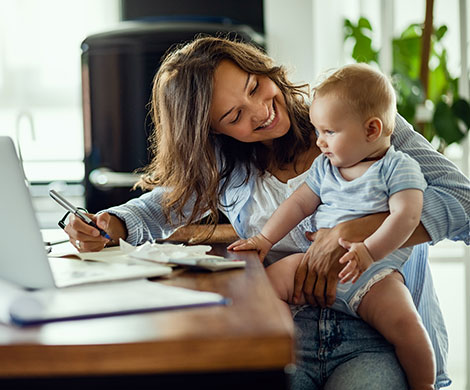 Mother and child sitting at desk in home office