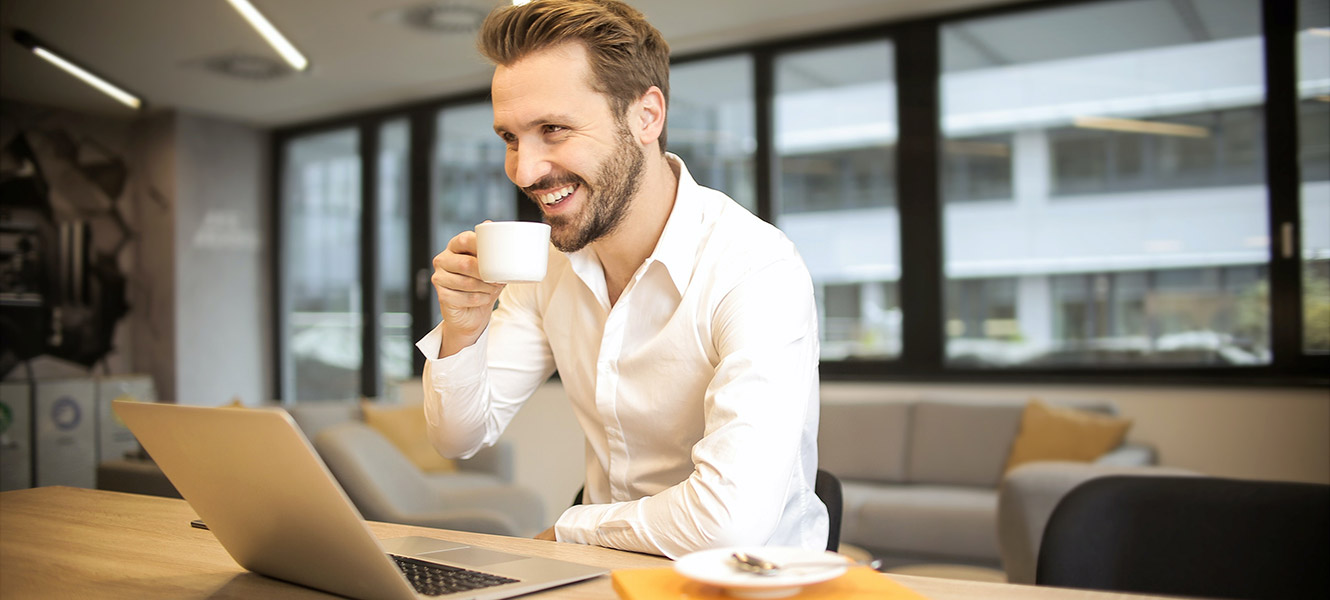 Man having coffee while meet virtually with colleagues